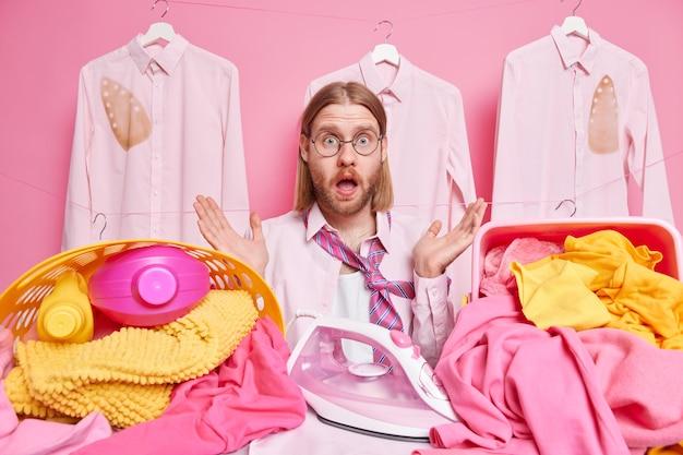 L'uomo imbarazzato perché ha molto lavoro da fare stira il bucato a casa sta vicino all'asse da stiro indossa occhiali rotondi non sa da dove cominciare