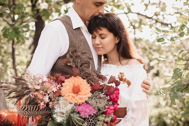 Un uomo abbraccia una ragazza con un bouquet in mano. dolce abbraccio di innamorati