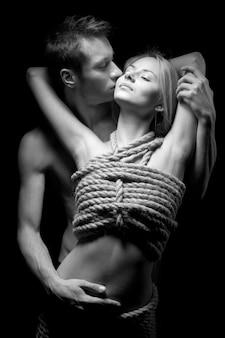 Uomo che abbraccia e bacia il suo partner di donna con il corpo nudo coperto di corde in camera oscura