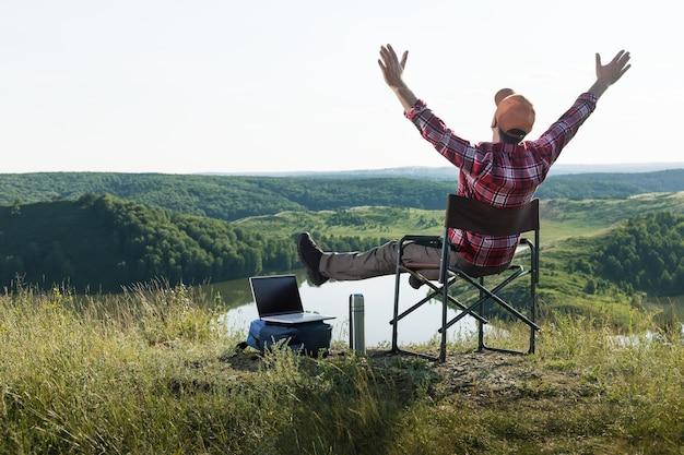 Mani alzate felici emotive dell'uomo che godono della natura. concetto di lavoro a distanza - uomo adulto felice con il computer portatile in cima alla montagna.