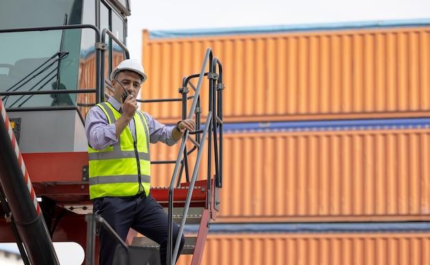 Ingegnere uomo che utilizza un walkie-talkie nel cantiere navale, il lavoratore industriale controlla il caricamento dei container tramite walkie-talkie nelle attività di import-export.