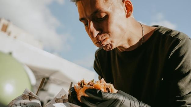 L'uomo si gode il festival del cibo di strada all'aperto, l'evento della birra e dell'hamburger. battaglia di hamburger