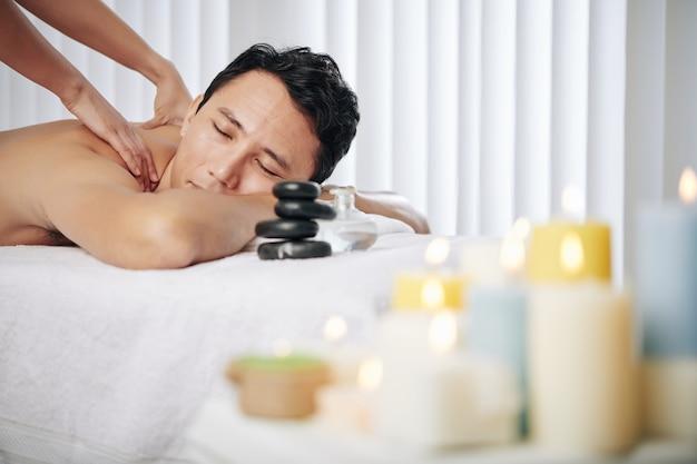 Uomo che gode del massaggio alla schiena