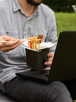 L'uomo si gode il cibo che ha ordinato. pranzo al parco all'aperto. cucina asiatica. concetto di consegna del cibo, fast food, mockup.