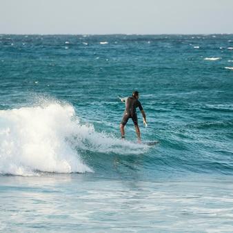 L'uomo si gode il suo tempo sulla tavola da surf
