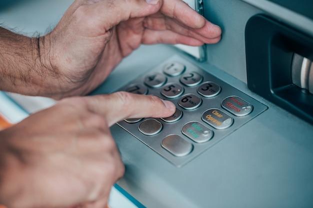 Uomo che immette un codice pin per la sua carta di credito presso un bancomat, prelievo di denaro, concetto di finanza