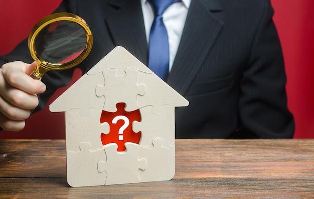 Un uomo esamina una casa con un puzzle mancante all'interno valutazione della proprietà trovare problemi