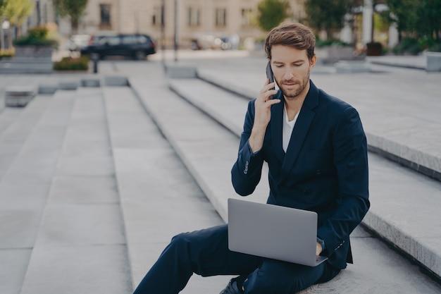 Il lavoratore esecutivo dell'uomo parla al cellulare con il partner commerciale utilizza un computer portatile moderno