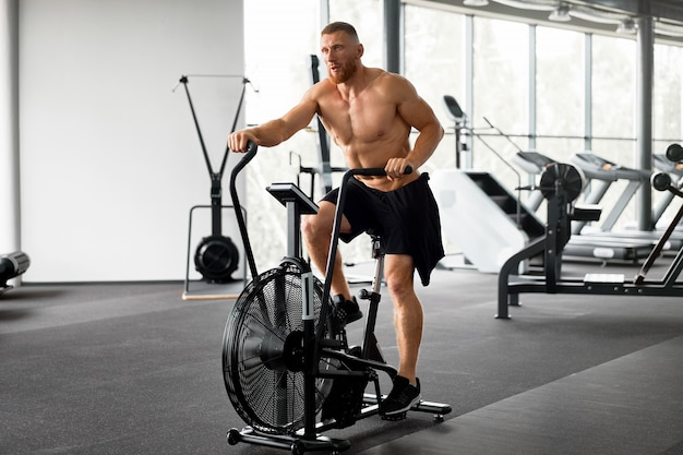 Uomo cyclette palestra ciclismo allenamento fitness.