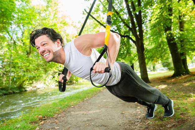 Uomo che si esercita con l'imbracatura dell'istruttore della sospensione nel parco cittadino sotto gli alberi estivi per il fitness sportivo