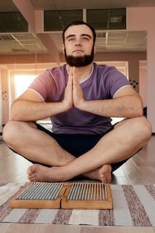 Uomo che esercita yoga meditazione seduta mani unite sul pavimento vicino a una tavola di sadhu