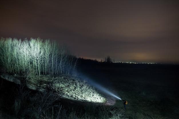 Uomo che esplora all'aperto e punta la torcia elettrica alla foresta di notte