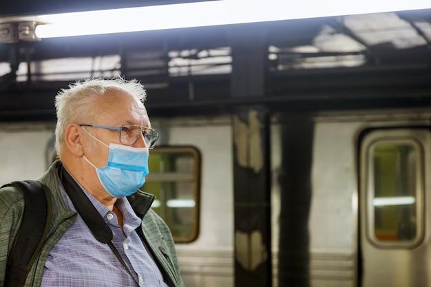 Maschera usa e getta uomo in faccia nella stazione della metropolitana covid-19 epidemia di coronavirus pandemia sul treno tubo della metropolitana assistenza sanitaria maschile treno soft focus