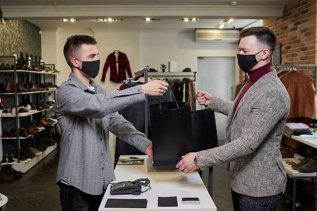 Un uomo con una maschera facciale per evitare la diffusione del coronavirus sta prendendo il suo acquisto da un venditore in un negozio di abbigliamento. un commesso maschio sta regalando una seconda borsa con dei vestiti a un cliente in una boutique