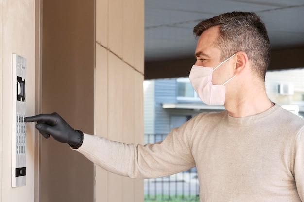 Un uomo in maschera e guanti compone il codice al citofono ed entra nel portico del suo appartamento. concetto di coronavirus covid-19 pandemico