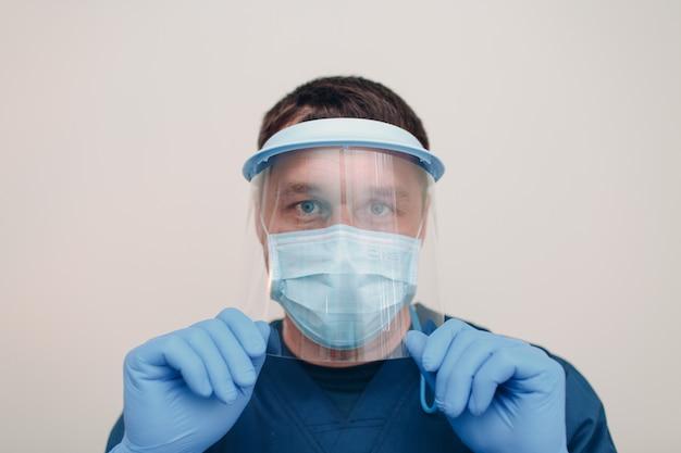 Maschera chirurgica medica uomo in faccia con maschera protettiva trasparente e guanti.