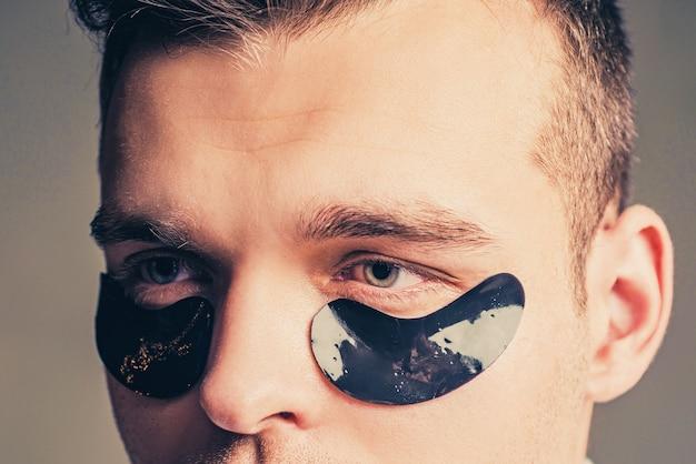 Fronte dell'uomo con fiocchi sotto gli occhi. fiocchi di uomo. patch sotto gli occhi chiusi per l'uomo. digitopressione