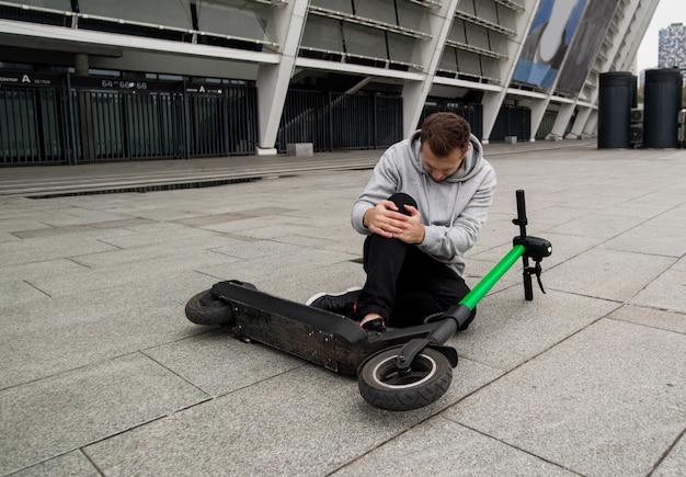 Uomo caduto dallo scooter tenendo il ginocchio e provando dolore. scooter elettrico verde che si trova sull'asfalto. uomo alla moda in felpa con cappuccio grigia si siede per terra e ha dolore al ginocchio. concetto di trasporto ecologico.