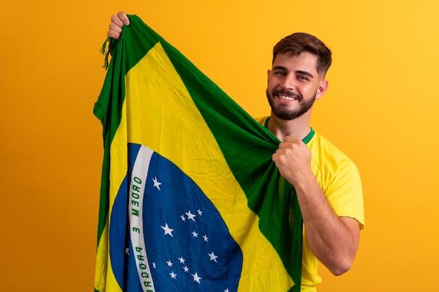 Fan dell'uomo che tiene uno sfondo giallo bandiera brasiliana. colori del brasile sullo sfondo, verde, blu e giallo. elezioni, calcio o politica.