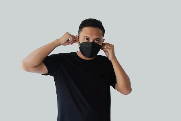 Uomo che allaccia la maschera facciale kn95 nell'orecchio