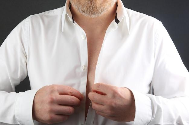 L'uomo allaccia i bottoni sulla sua camicia