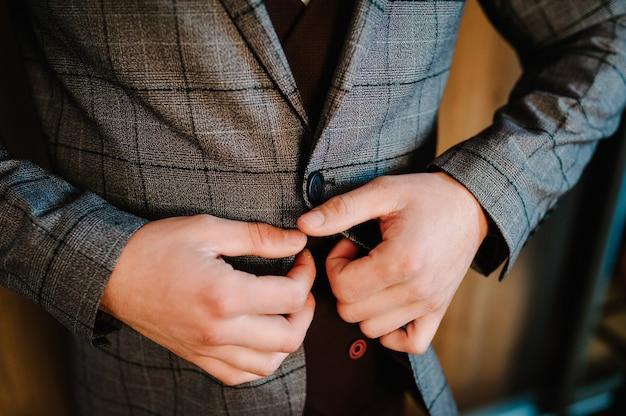 L'uomo allaccia la giacca con i bottoni. lo sposo in abito, camicia è in piedi sullo sfondo della camera. avvicinamento.