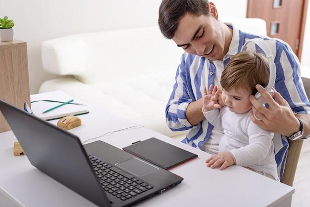 Uomo, padre in camicia blu con bambino in braccio è seduto al laptop e tavoletta grafica, bambino in cuffia, concetto di paternità, lavoro a distanza in condizioni di quarantena