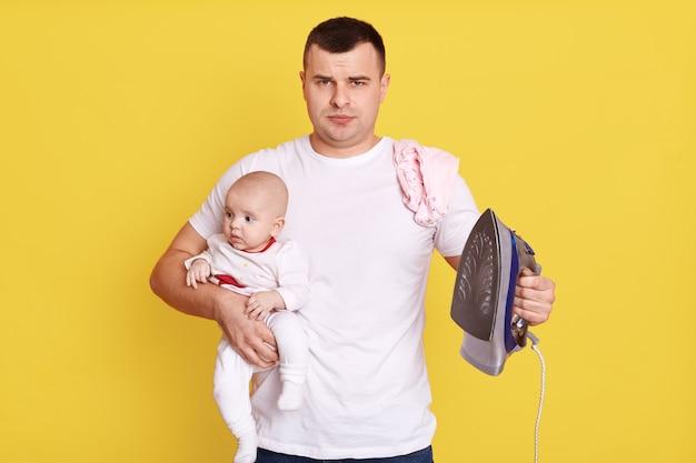 L'uomo padre con il ferro e il bambino in mano, ha bisogno di fare molto lavoro, con espressione perplessa, indossa abiti casual, bel ragazzo con bambino che fa le faccende domestiche.