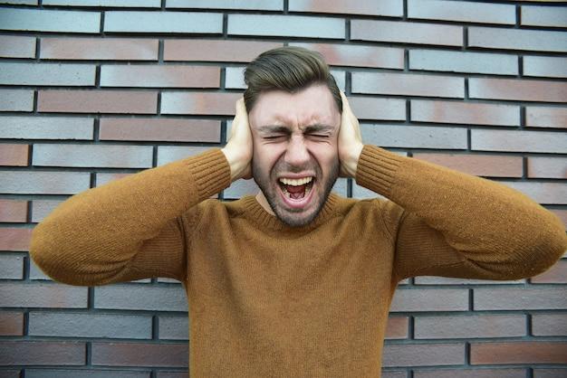 Uomo che prova emozioni dolorose, urla, testimone della morte di un caro amico, essere infelice e devastato, tenere i palmi sulla testa, urlare per il dolore e lo stress, in piedi infelice sul muro di mattoni marroni