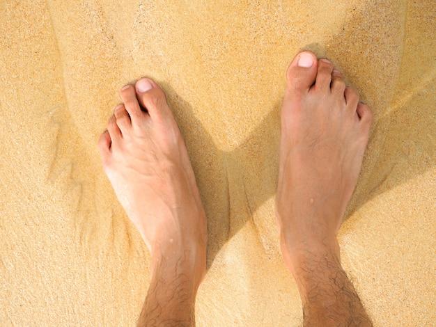 Un uomo piedi, gamba sulla sabbia nella bellissima spiaggia, day-off concept