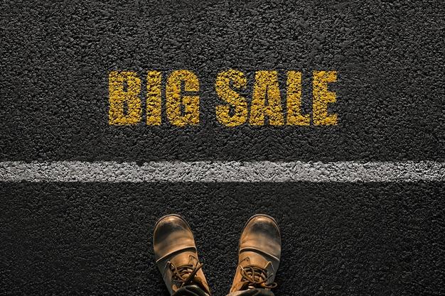 Piedi di uomo con scarpe di cuoio cammina vicino alla linea con il testo giallo grande vendita sul marciapiede, vista dall'alto. concetto di vendita e marketing. entra nello shopping