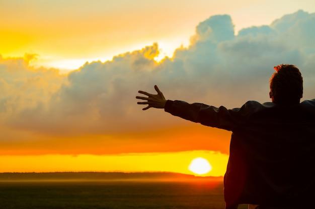 Uomo in campo sul bellissimo tramonto. silhouette di un giovane uomo con le braccia aperte