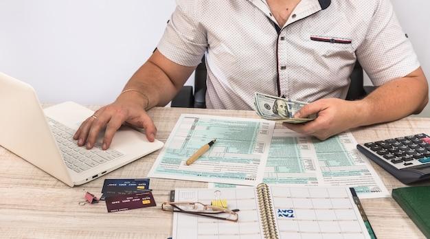 Uomo che compila il modulo fiscale 1040 sul posto di lavoro. esecuzione di calcoli fiscali. avvicinamento
