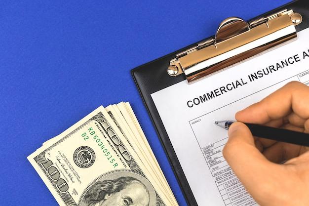 Uomo che riempie la polizza assicurativa commerciale. desktop aziendale con appunti, soldi e penna. sfondo blu e foto vista dall'alto