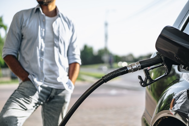 Uomo che riempie benzina in auto alla stazione di servizio