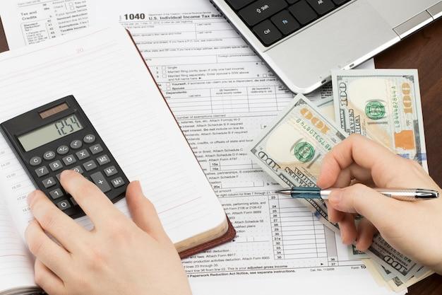 Uomo che compila il modulo fiscale degli stati uniti. modulo fiscale noi concetto di riempimento a mano dell'ufficio del reddito d'impresa.