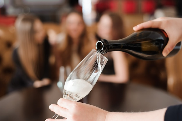 L'uomo riempie i bicchieri di champagne per tre belle giovani donne nel ristorante