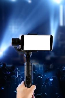 Uomo che riprende con uno smartphone con schermo vuoto utilizzando uno stabilizzatore cardanico, isolato su uno spettacolo musicale. messa a fuoco selettiva.