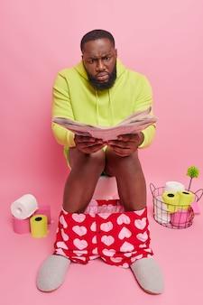 Un uomo scopre notizie da un giornale fresco posa sul water soffre di stitichezza indossa una felpa con cappuccio boxer e pantofole trascorre il tempo libero nella toilette