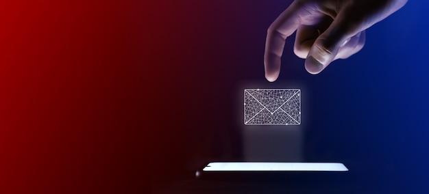Il dito dell'uomo fa clic sull'icona della lettera di posta elettronica aperta. più il simbolo per l'interfaccia utente di progettazione del tuo sito web. che è una proiezione virtuale da un telefono cellulare. neon, luci blu rosse.