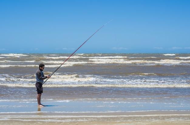 Uomo che pesca sulla spiaggia di pesca sportiva