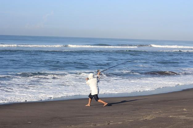 Uomo che pesca in mare dalla spiaggia