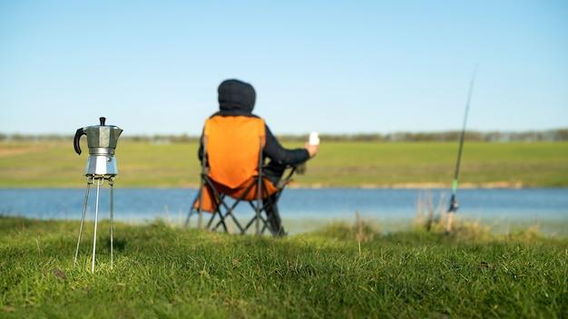 Un uomo sulla pesca seduto su una sedia e con in mano una tazza, caffettiera in primo piano