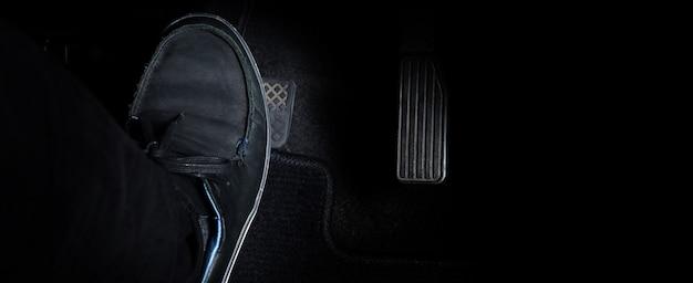 Piede dell'uomo e pedale dell'acceleratore e del freno all'interno dell'auto o del veicolo e copia dello spazio di colore nero