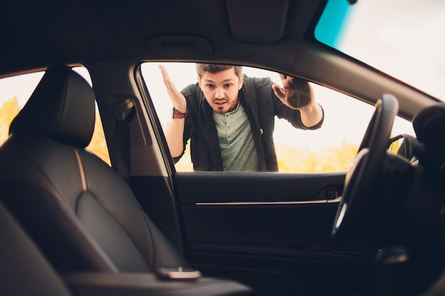 L'uomo ha dimenticato la chiave all'interno della sua auto. concetto di trasporto, criminalità e proprietà