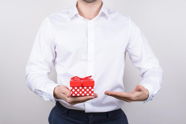 Uomo in abiti da cerimonia dimostrando piccolo giftbox isolato