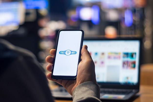 Libero professionista uomo tiene uno smartphone con connessione internet gratuita nelle sue mani sullo sfondo di un laptop.