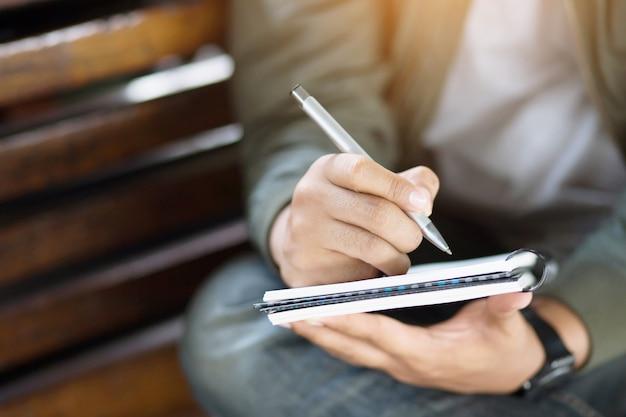 Giornale di scrittura della mano di lavoro libero professionista dell'uomo sul piccolo blocco note del taccuino
