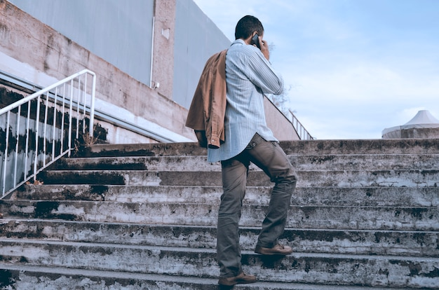 Uomo dal retro, parlando al cellulare sulle scale della città. un ragazzo casual e simpatico con smar