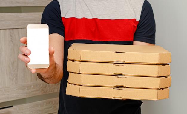 Uomo dal servizio di consegna che tiene le scatole e lo smartphone della pizza con derisione su. ordine alimentare su internet.